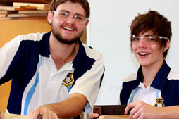 Two male students with safety glasses on.