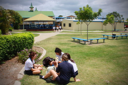 Female students sitting in a group on the grass in the school grounds.