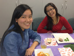 Two female students eating at table.