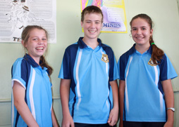 Three junior students laughing whilst posing.
