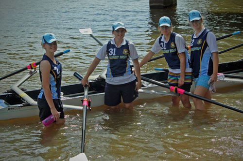 Four female students in sport uniform standing in water next to a row boat.